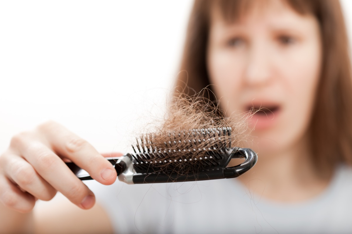 woman looking in shock at hair in her comb signs your metabolism is slow
