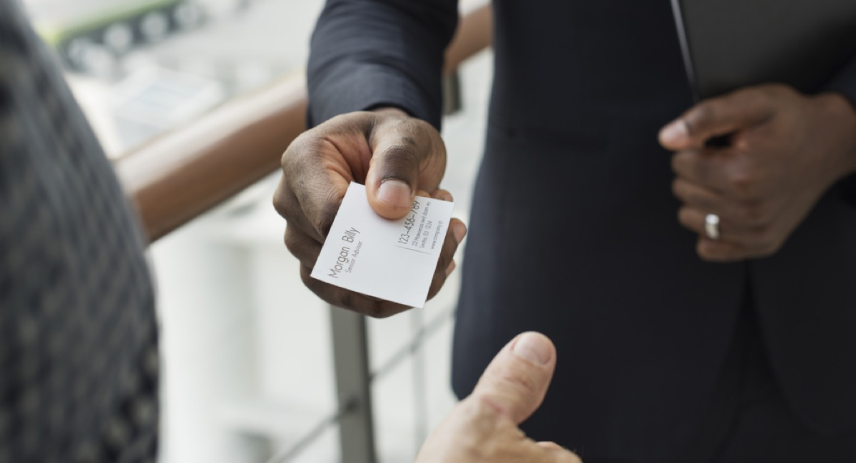woman offering coworker her business card, office etiquette