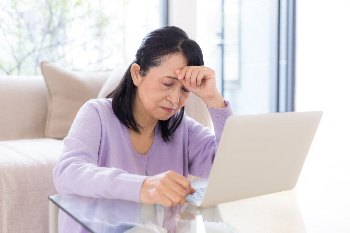 woman with a headache at a laptop