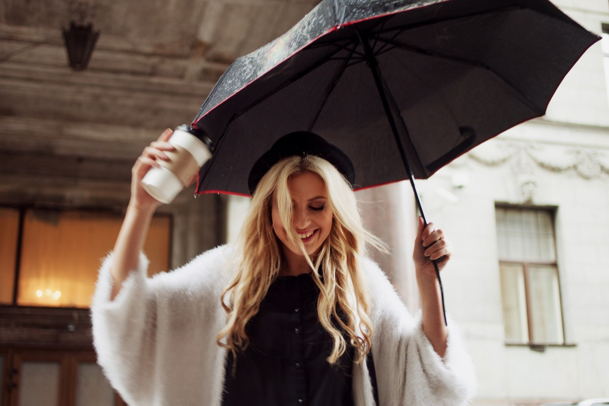 woman holding an umbrella and coffee