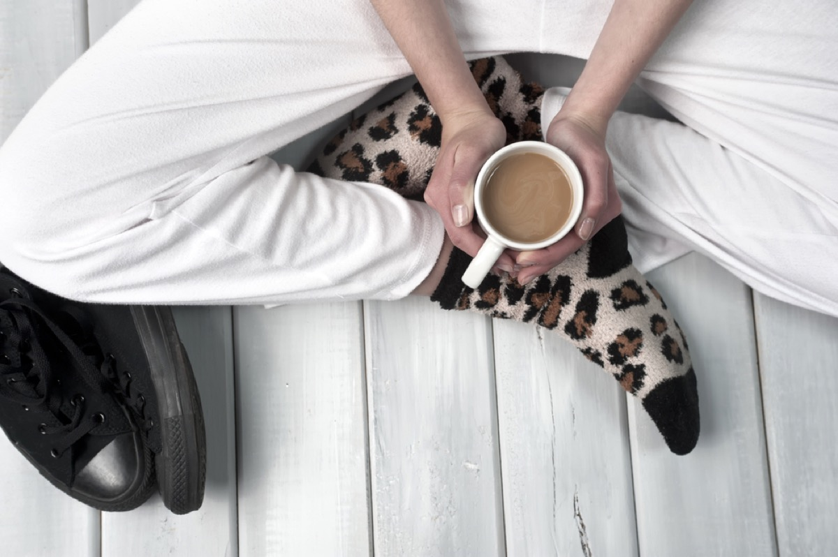 woman holding coffee in pajamas things you're doing that would horrify sleep doctors
