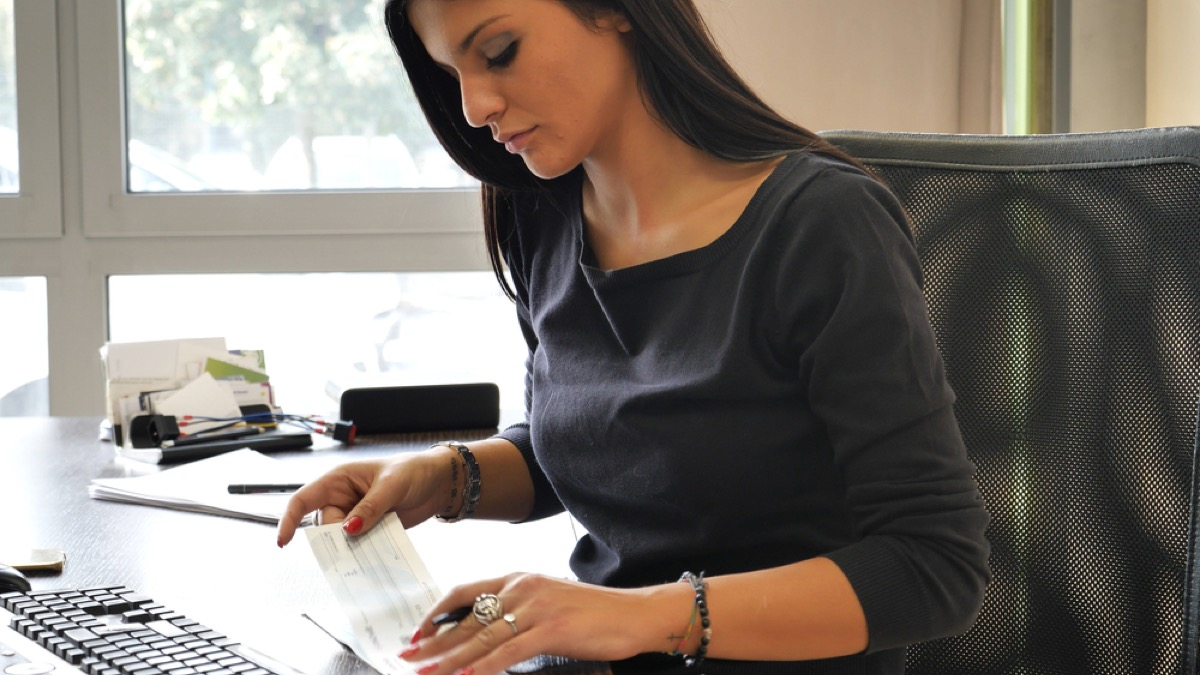 woman looking at paycheck amount, office etiquette