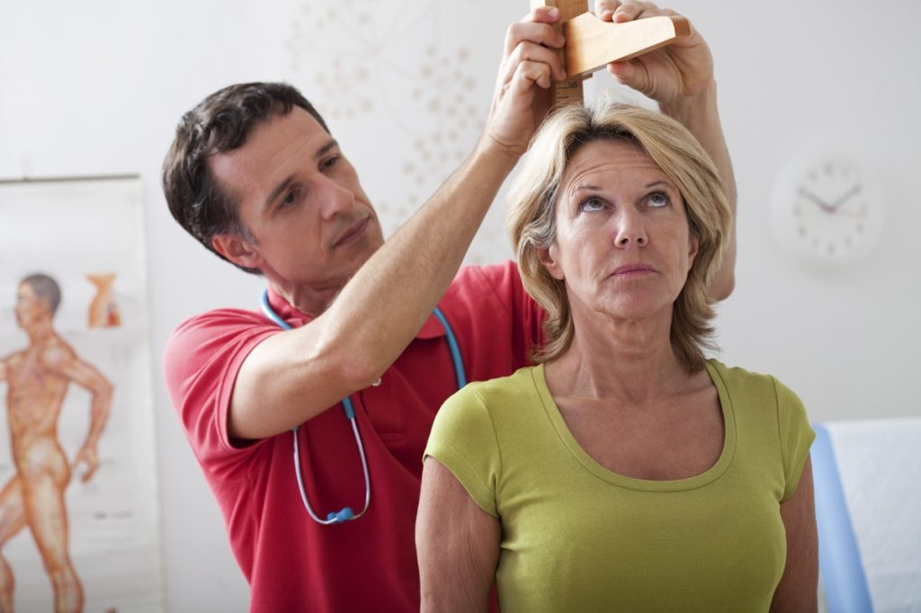 a doctor measuring a woman's height