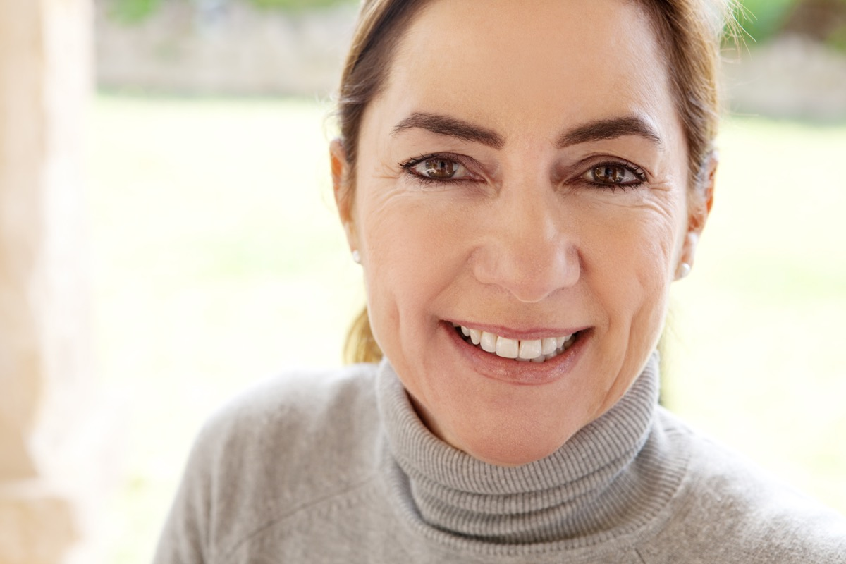 middle aged woman smiling and wearing a turtleneck