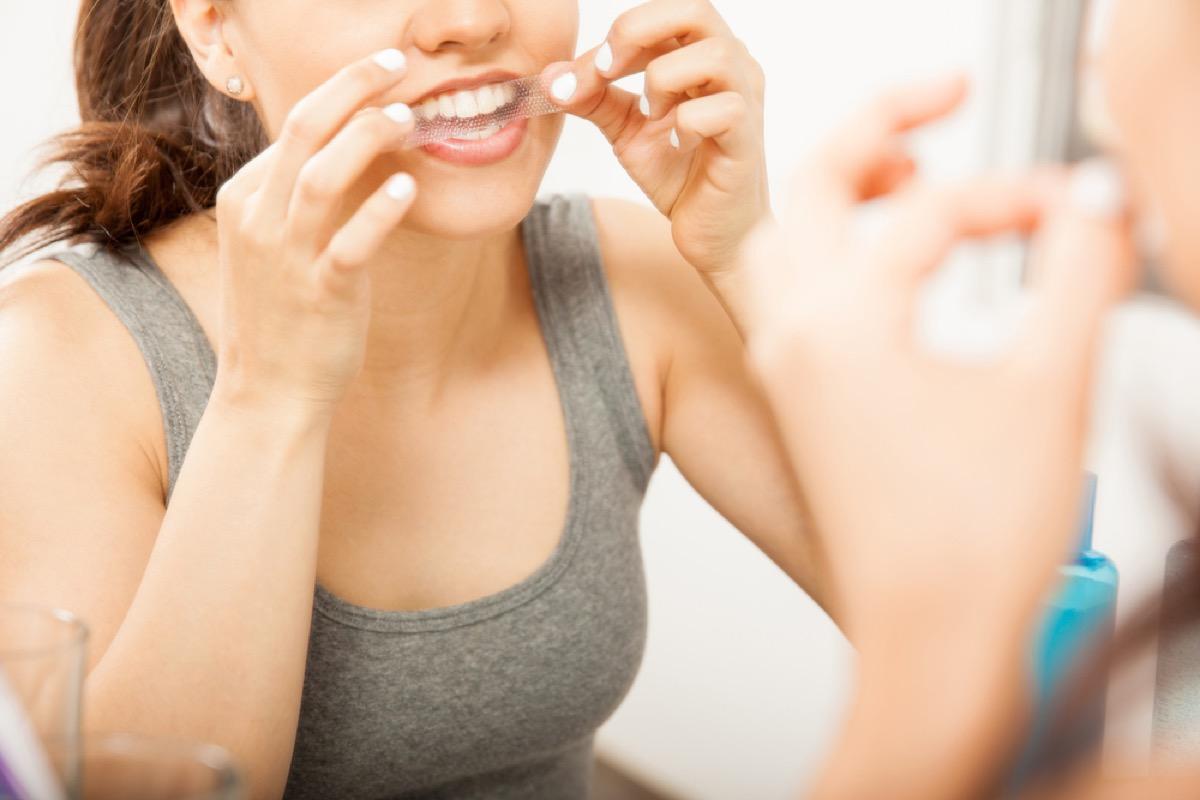 woman using tooth whitening strip, ways you're damaging teeth