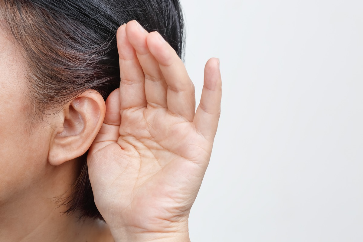 woman with gray hair cupping her ear because she is hard of hearing
