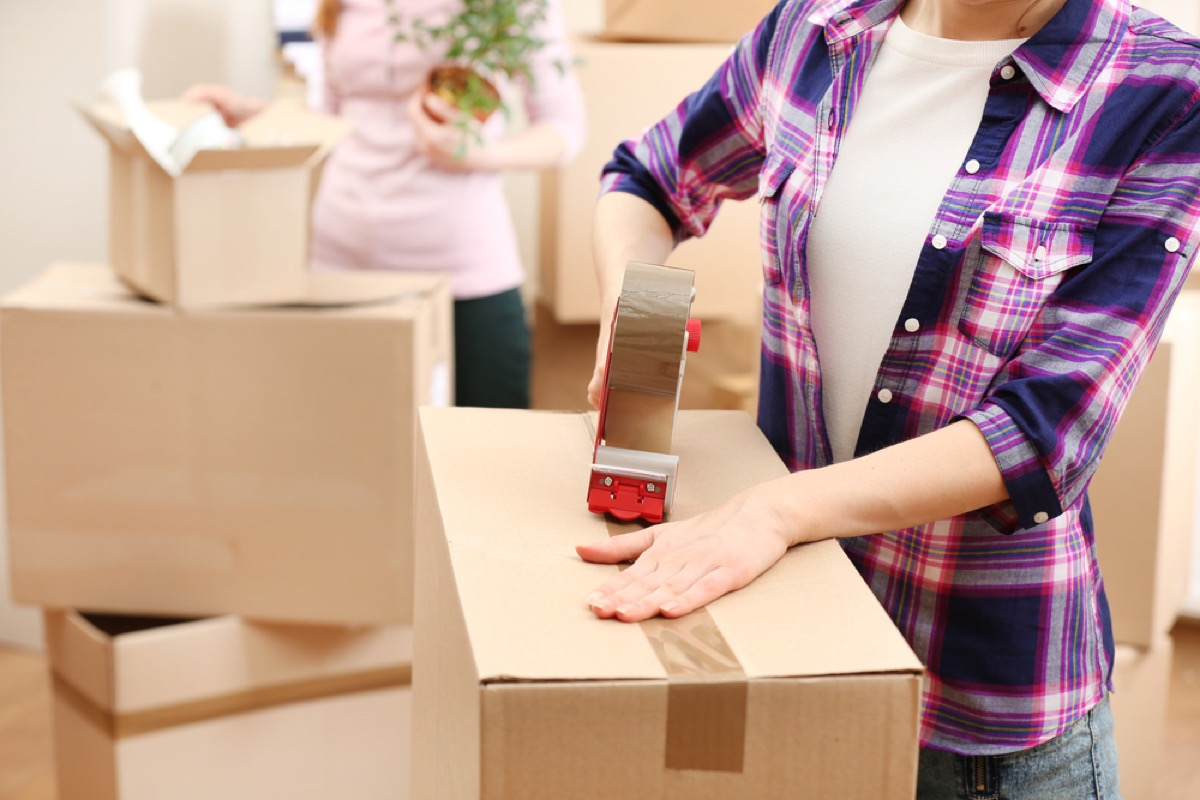 women taping moving boxes, downsizing your home