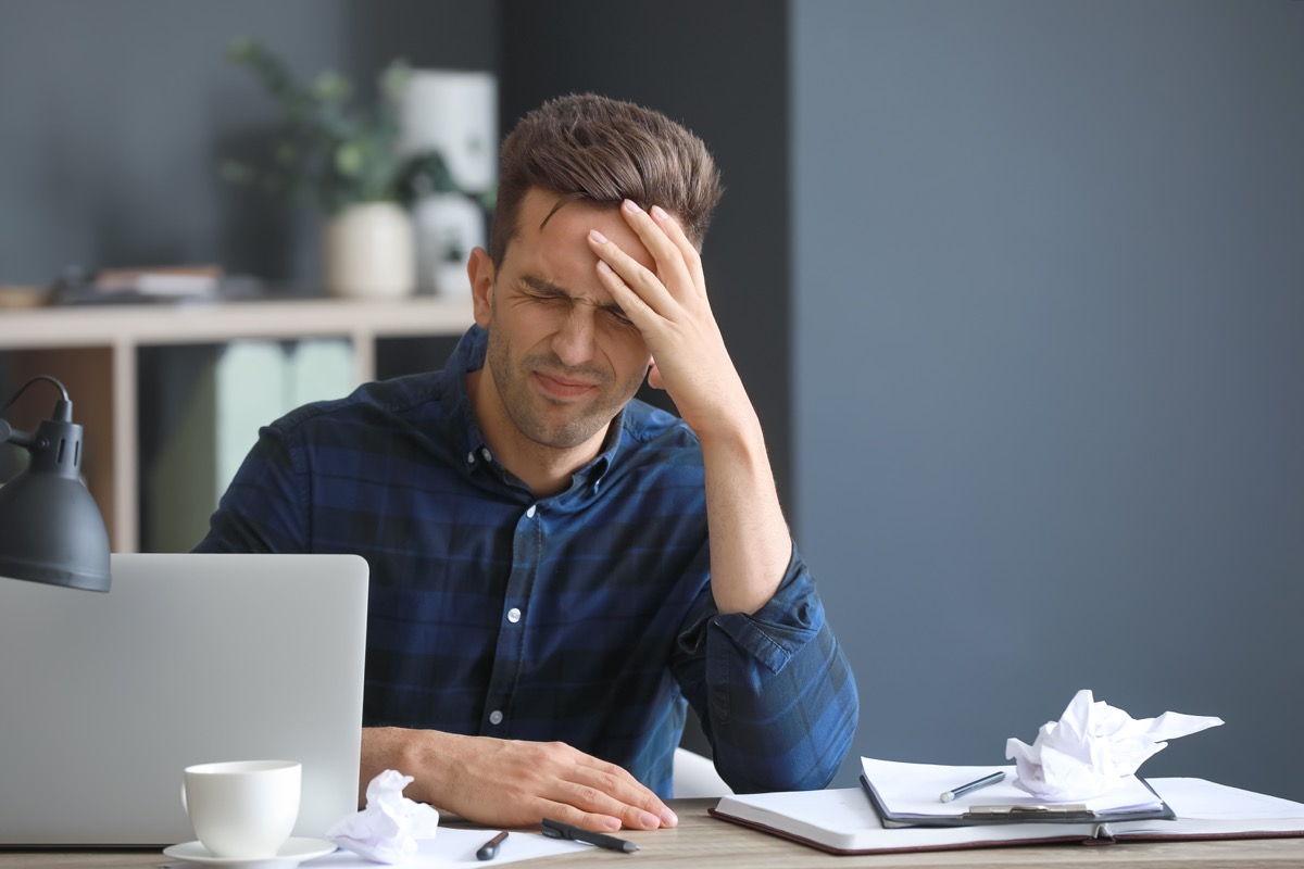 Man stressed and agitated while working at his desk