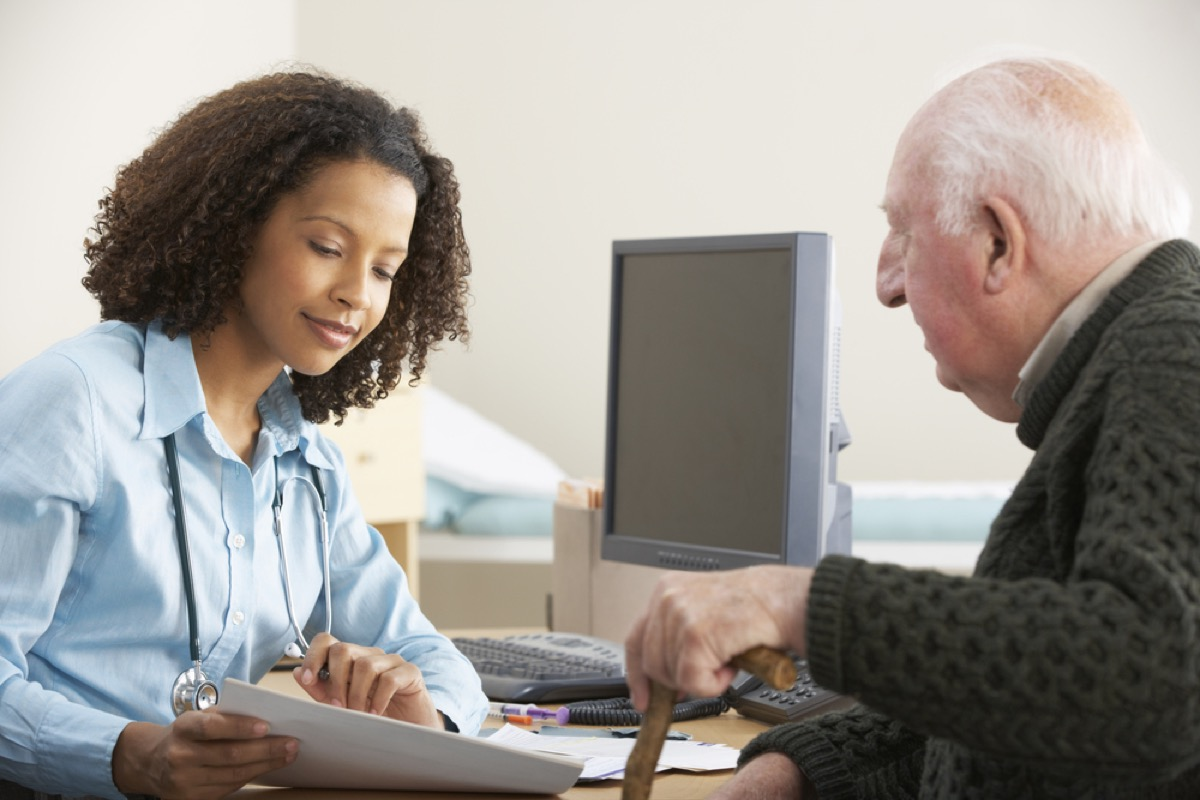 young black female doctor speaking to older white male patient, heart risk factors
