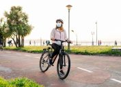 woman biking while wearing a mask