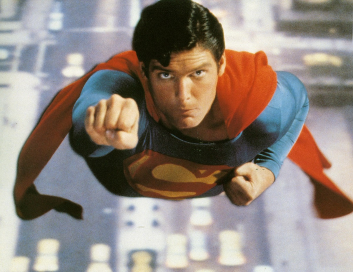 Christopher Reeve flies through the sky with a fist in the air as as Superman in 1978 Warner Bros film