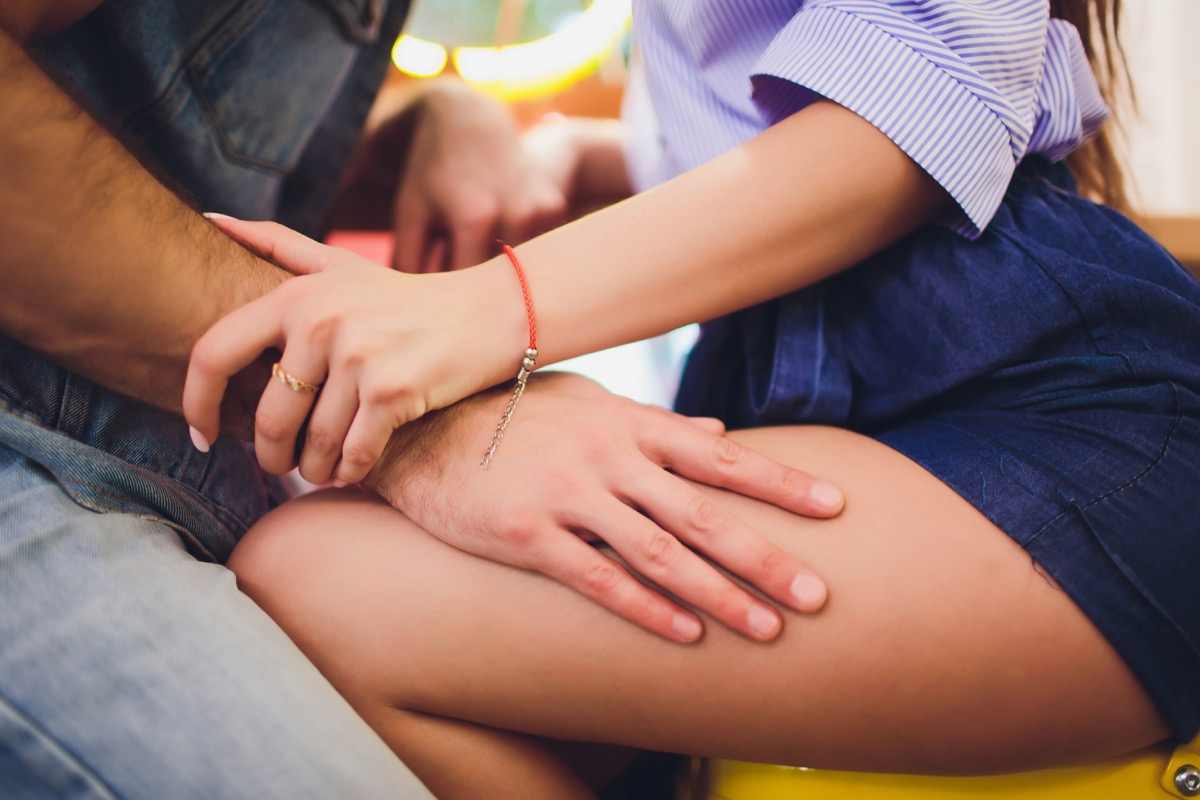 Man's hand on woman's thigh as they flirt in early stages of relationship, husband came out at bisexual