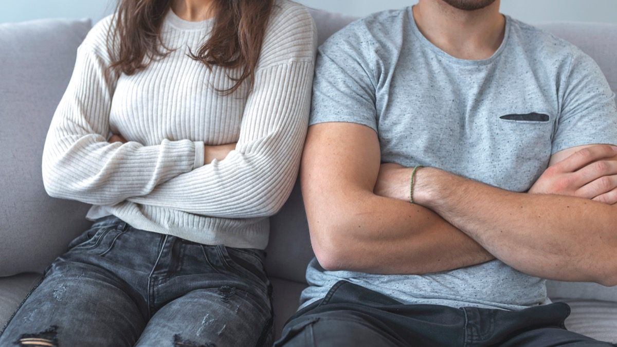 Young white couple, closeup of arms folded on couch, husband came out at bisexual