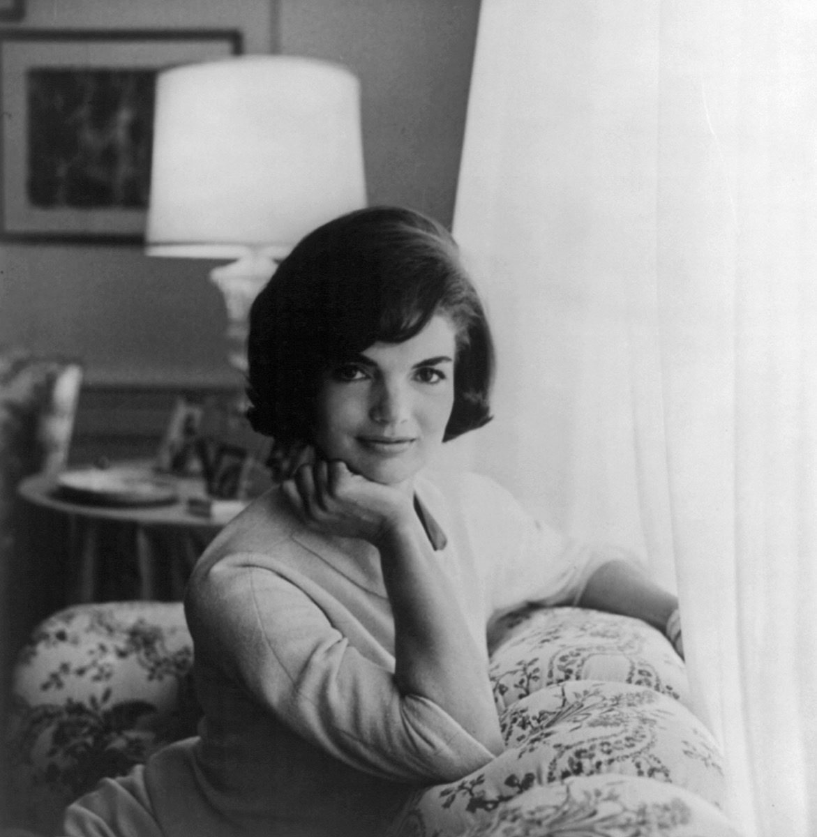 Portrait of Jackie Kennedy, Jacqueline Kennedy Onassis with hand on chin, leaning on couch