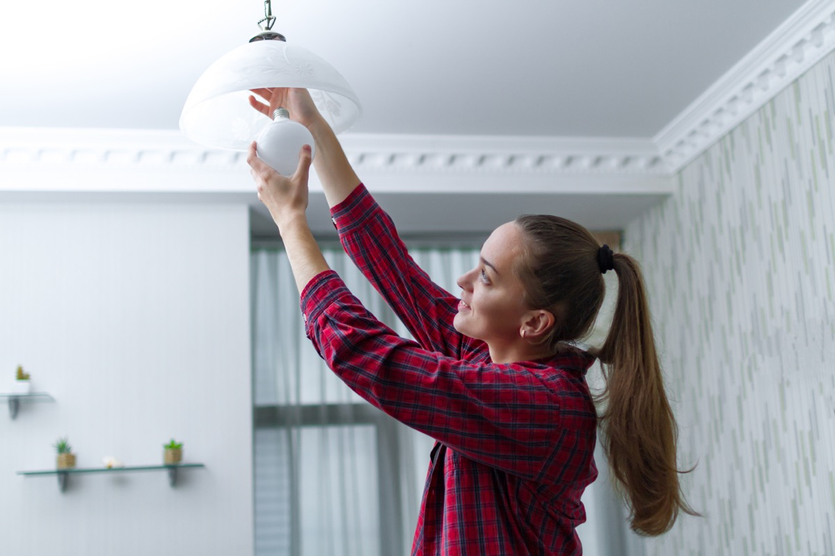 Woman adjust light fixture in house