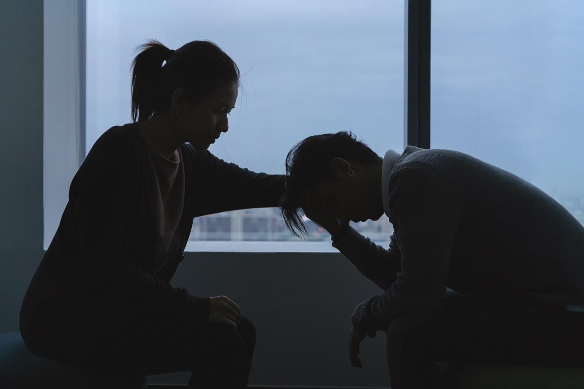 Depressed man and woman in dark room