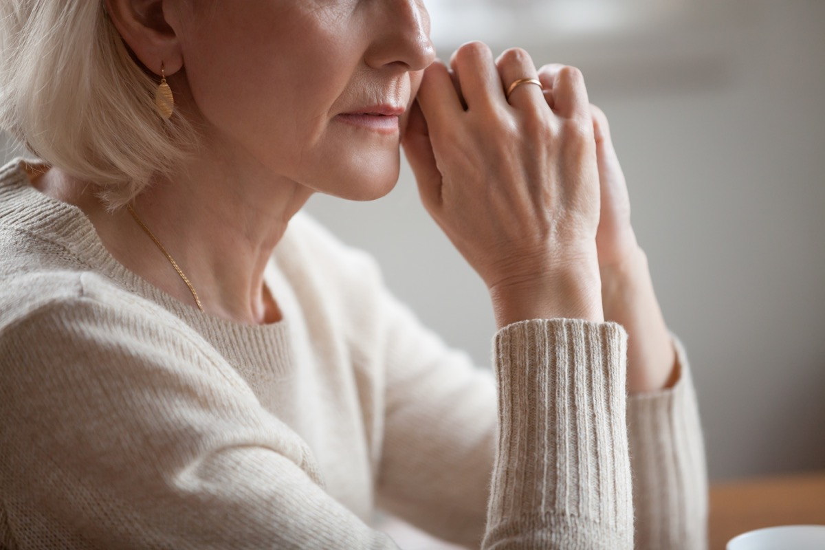 older woman sits with elbows on table, disappointed, divorce over 40, finding love again