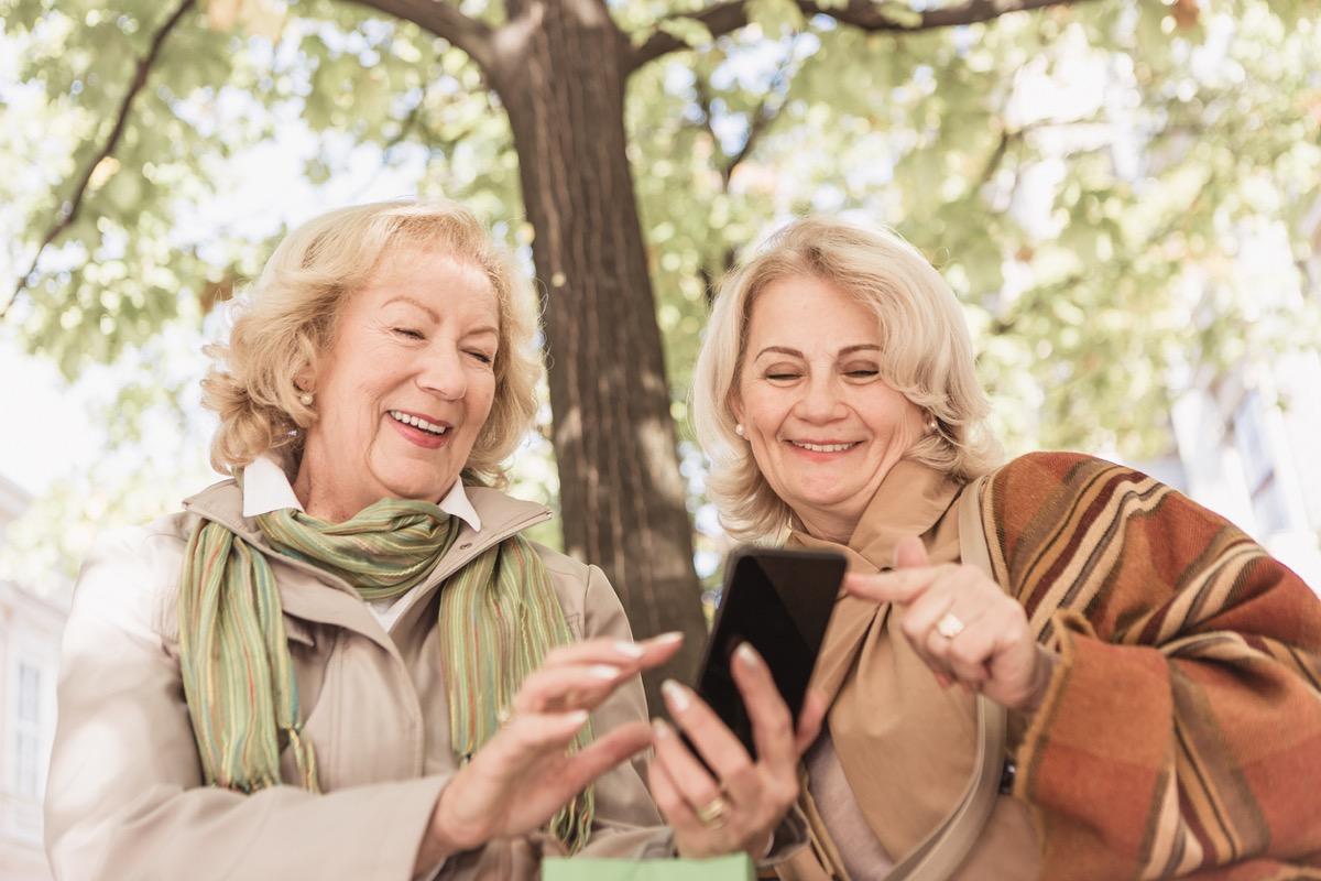 Two senior ladies in shopping. Resting, talking, laughing browsing mobile phone. Belgrade, Serbia, Europe