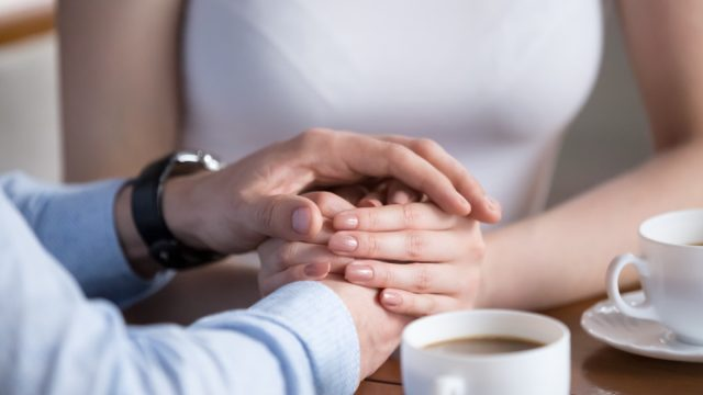 Woman puts hands on top of husband's, husband came out at bisexual