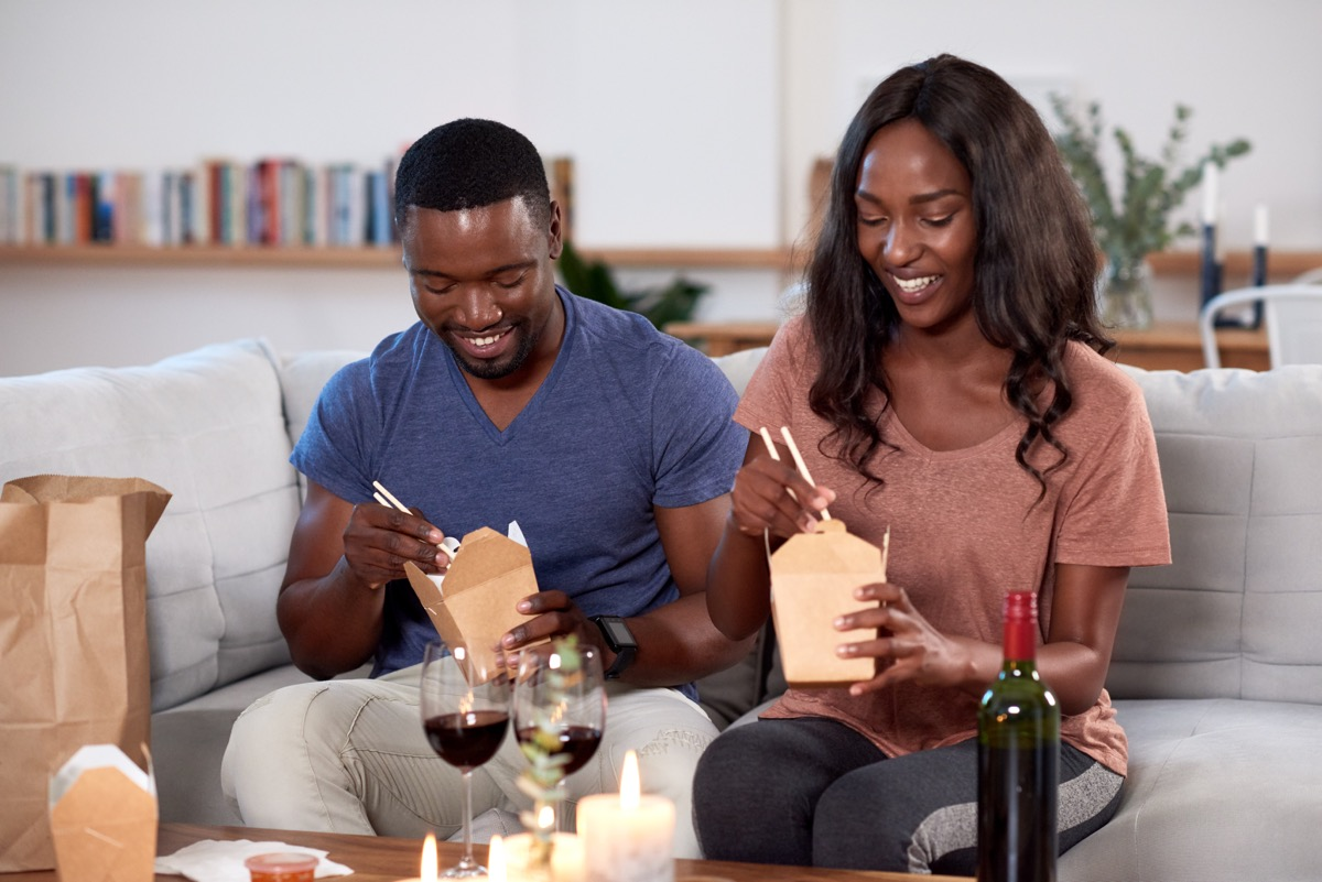 couple eating chinese food and wine on couch, best at-home date night ideas