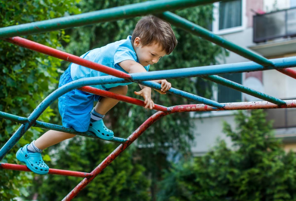 young child climbing on playground, backyard dangers