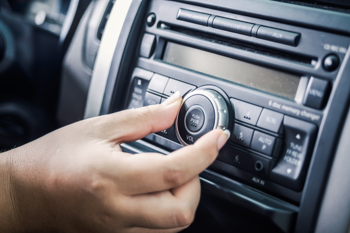 Close-up on hand of driver changing car radio dial