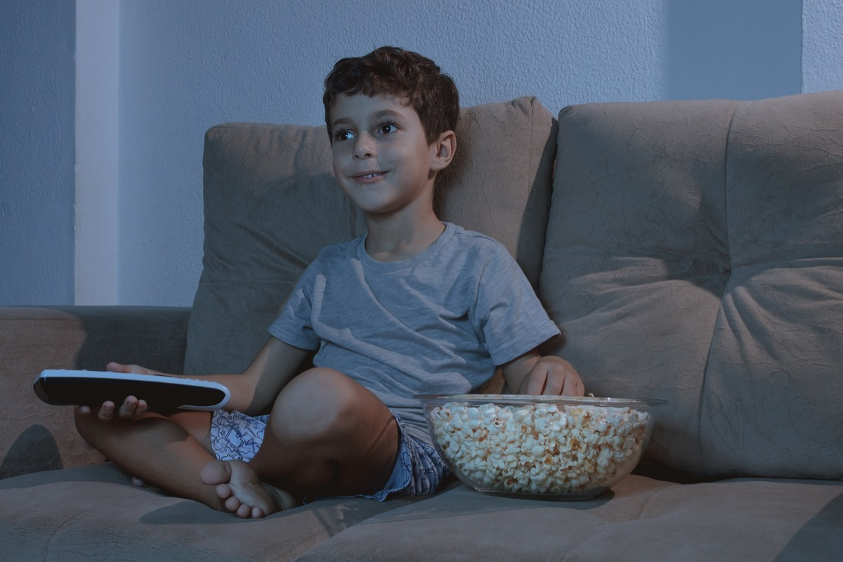 Child Watching TV and Eating Popcorn Late at night