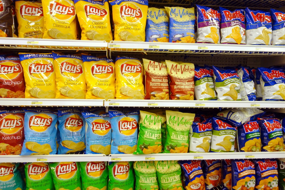 a chip aisle in the grocery store featuring junk food and snack food like lays and ruffles potato chips