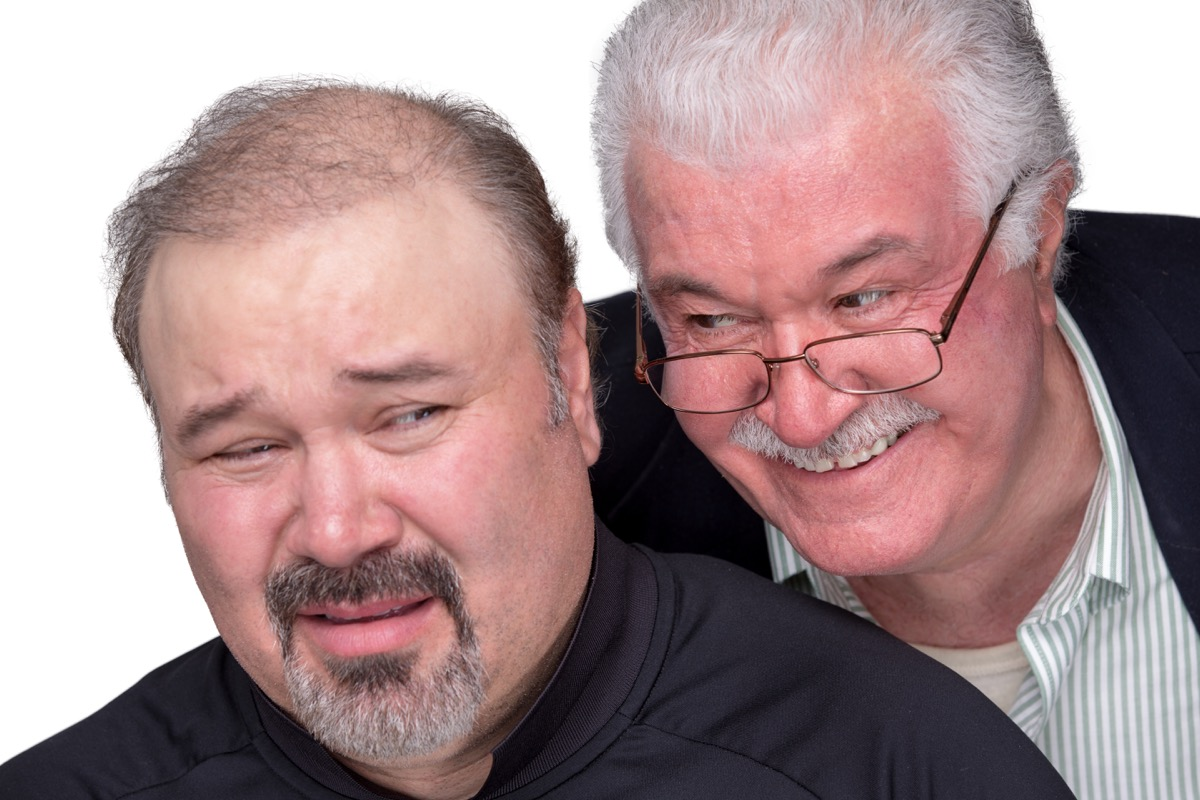 Man leaning over another man's shoulder, talking too closely