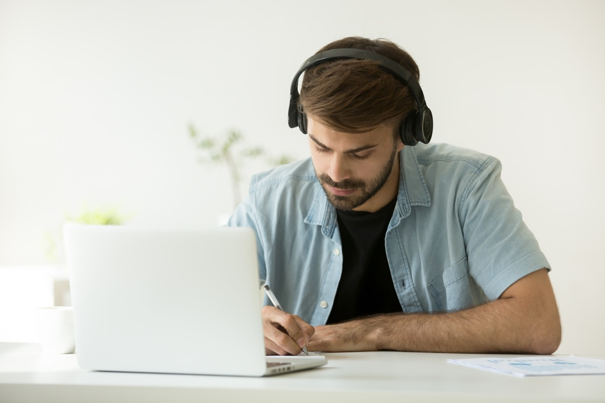 College Student Watching a Lecture on His Laptop With headphones ways college is different