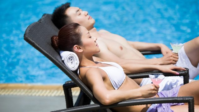 young couple sunbathing in affordable swimsuits by the pool