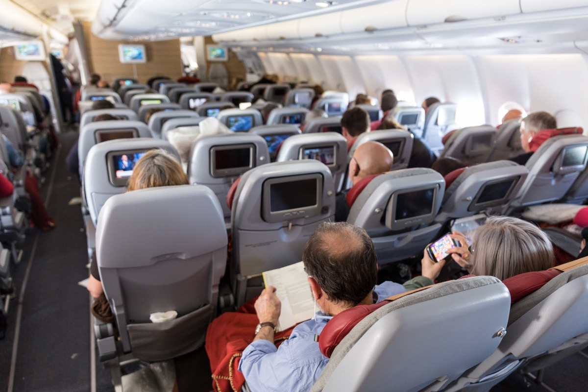 a crowded passenger cabin of an international flight