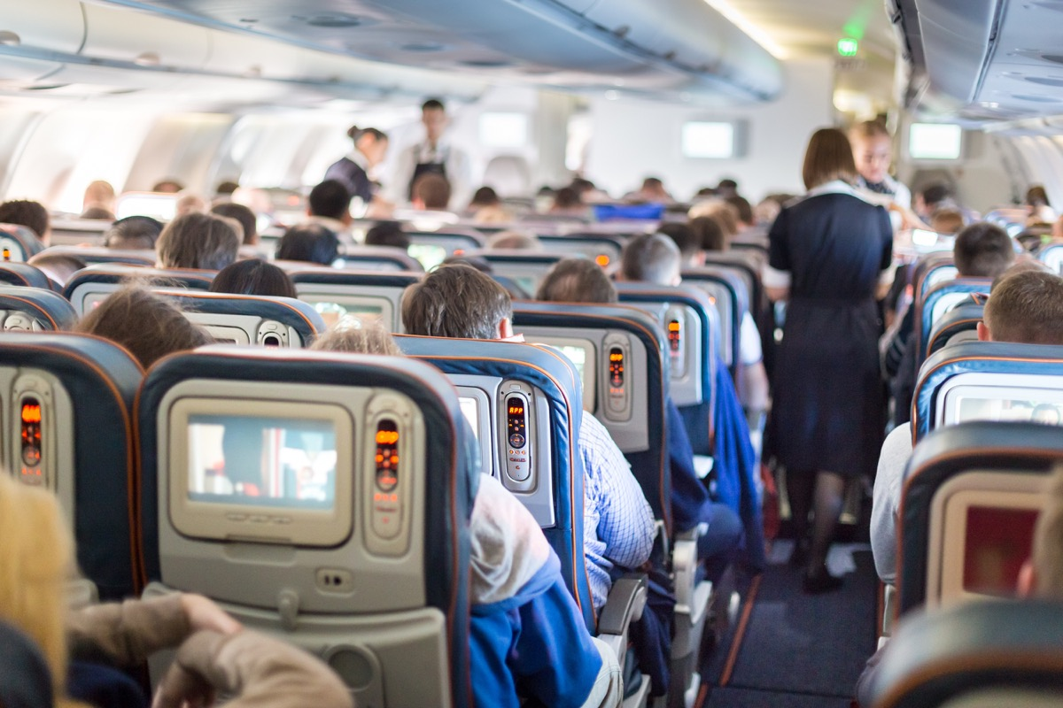 a flight attendant walks down the aisle of a crowded airplane