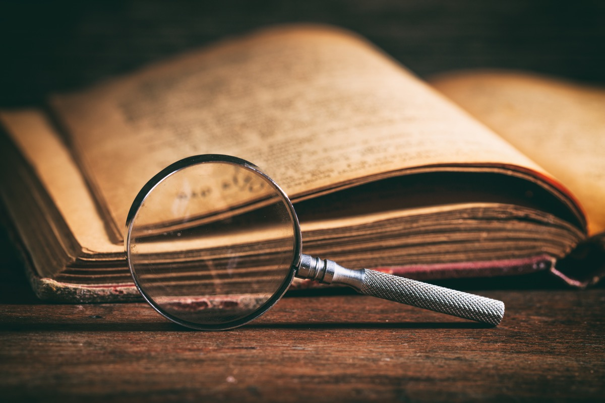 a dusty dictionary and a magnifying glass