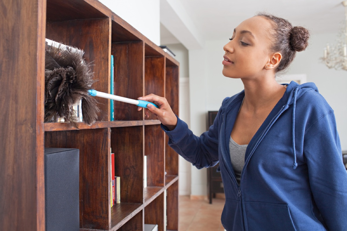 woman dusting bookshelf, how often you should replace your cleaning supplies