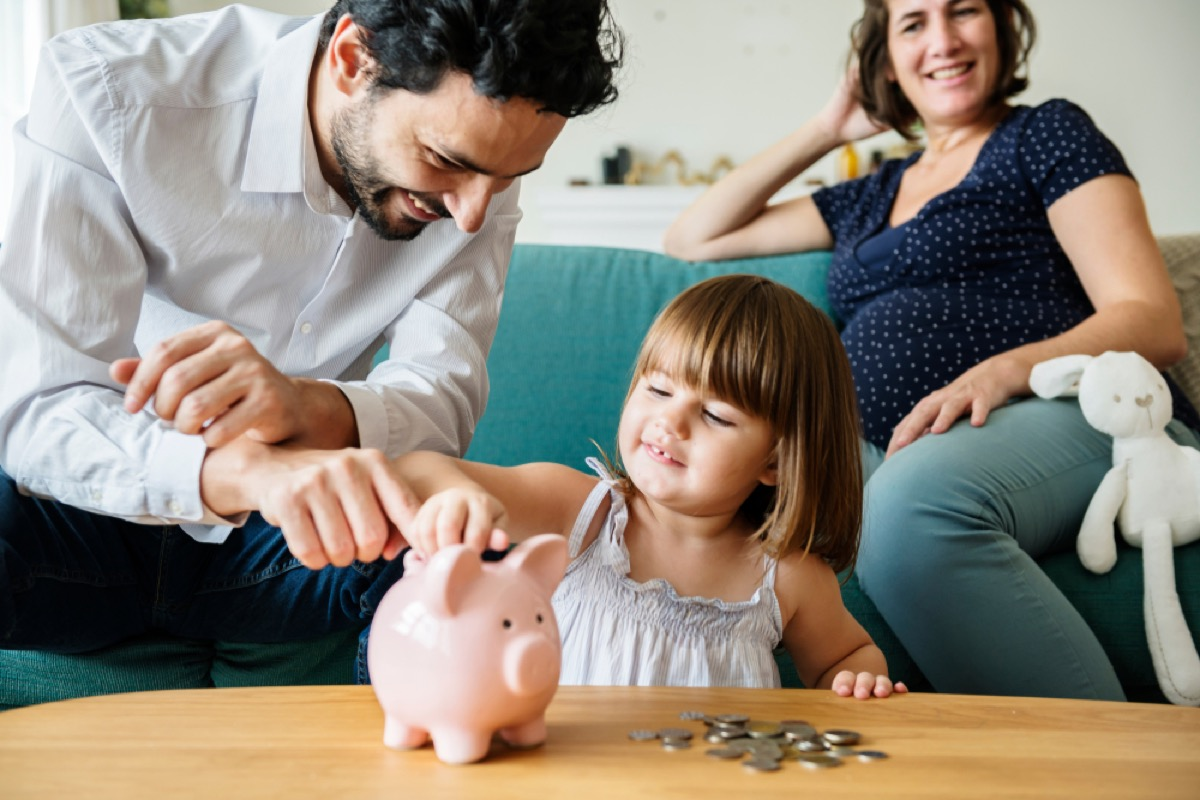 young girl putting coins in piggy bank, skills parents should teach kids