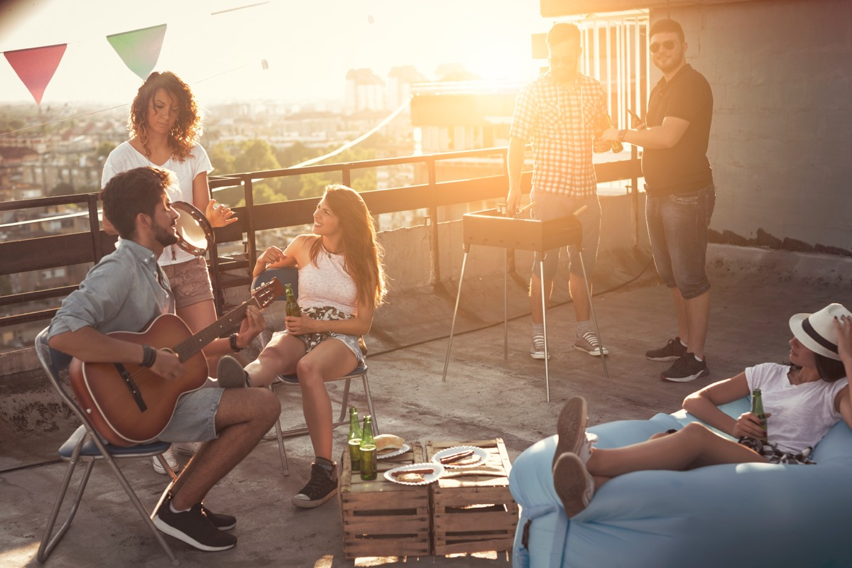 Guy playing guitar at a roof party