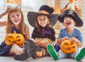 best halloween party games kids adults, kids sitting in costumes with pumpkins