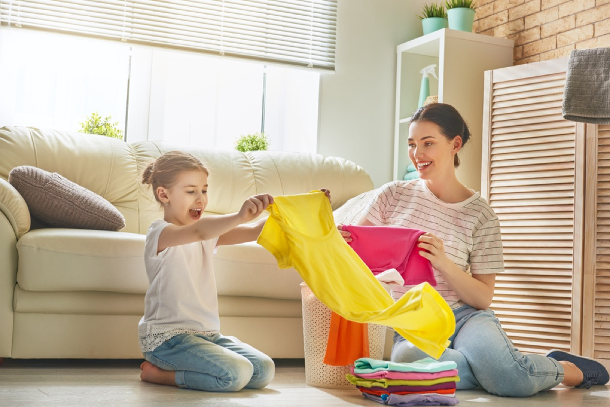 young girl and mother folding laundry, skills parents should teach kids