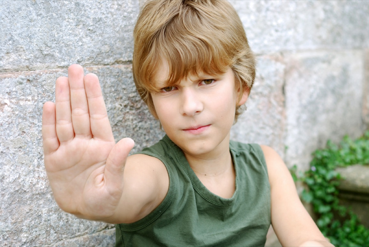 young boy putting hand up with palm out, skills parents should teach kids