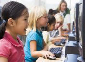 elementary school children in a computer lab with old technology
