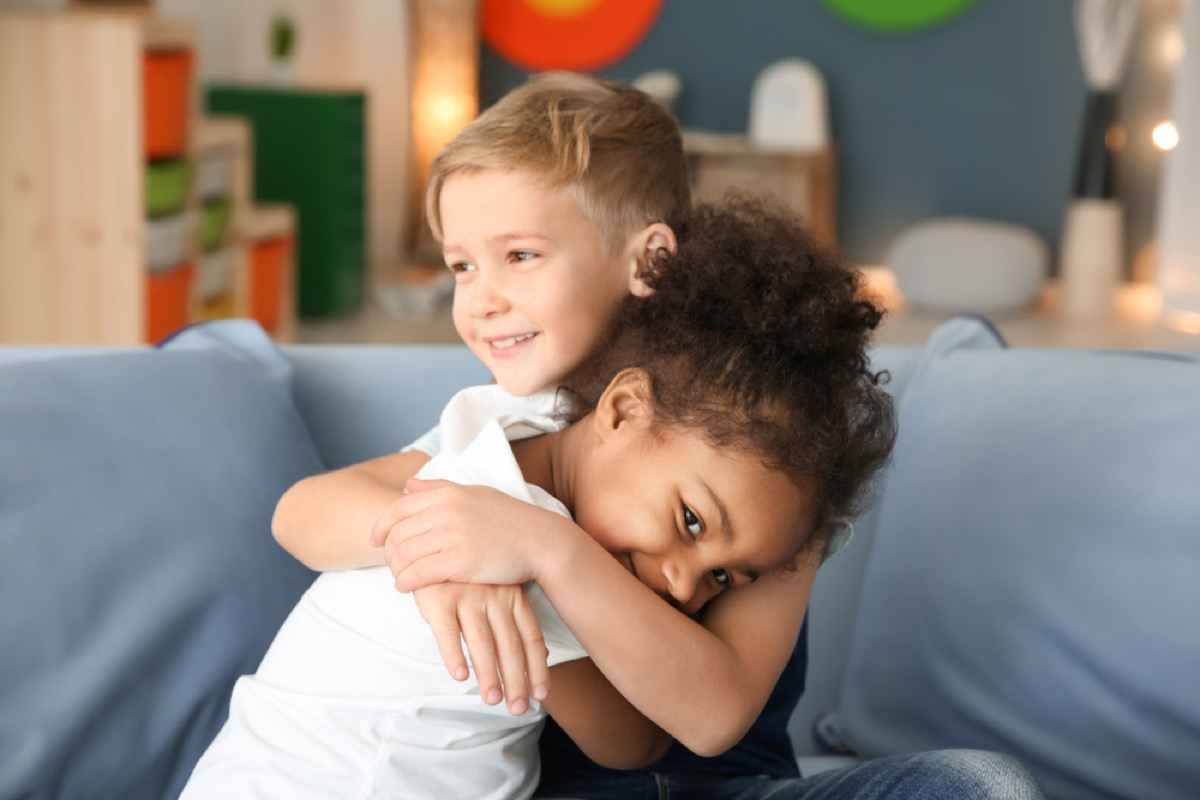 young girl and boy hugging on couch, skills parents should teach kids