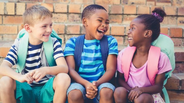 young kids with backpacks sitting outside talking, skills parents should teach kids