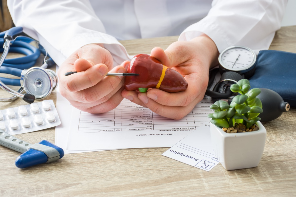 At doctors appointment physician shows to patient shape of liver with focus on hand with organ. Scene explaining patient causes and localization of diseases of liver, hepatobiliary system, gallbladder