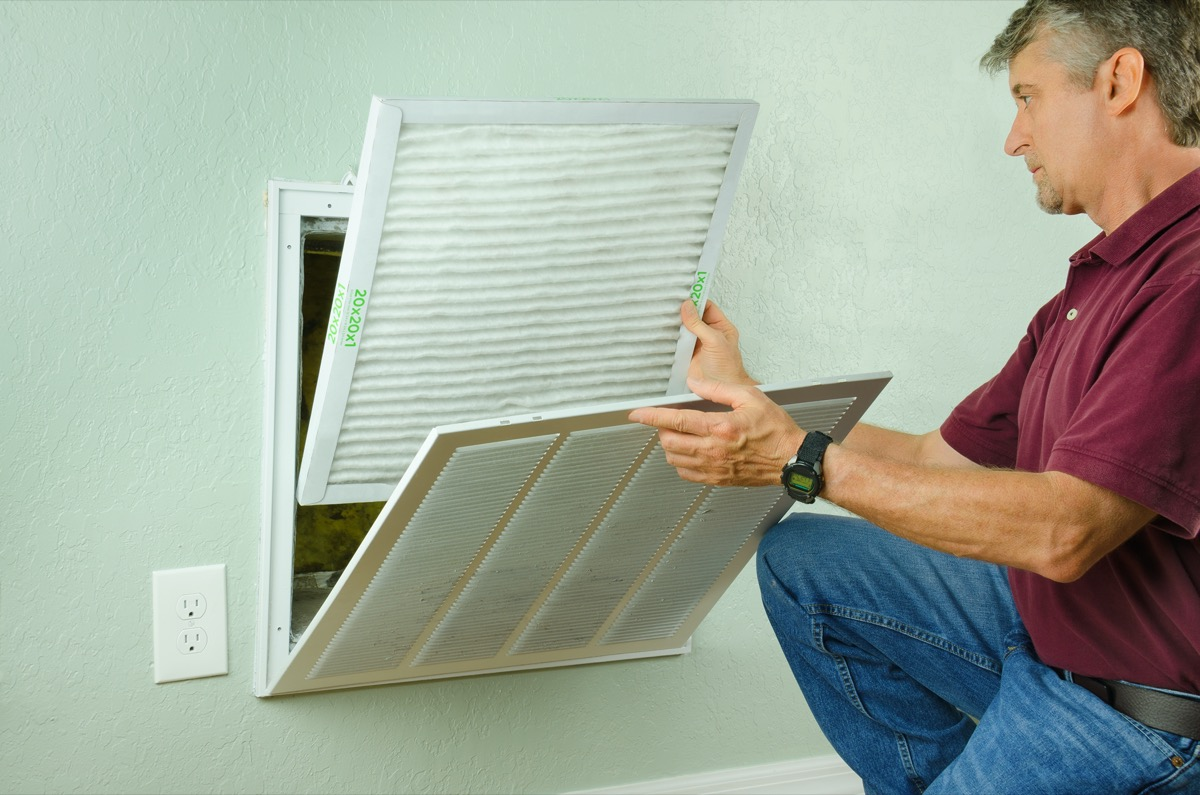 older white man changing air conditioner filter