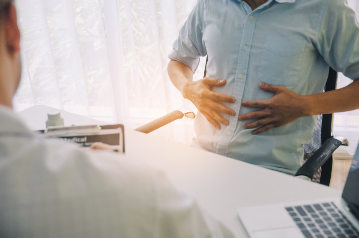 man holding stomach while talking to doctor
