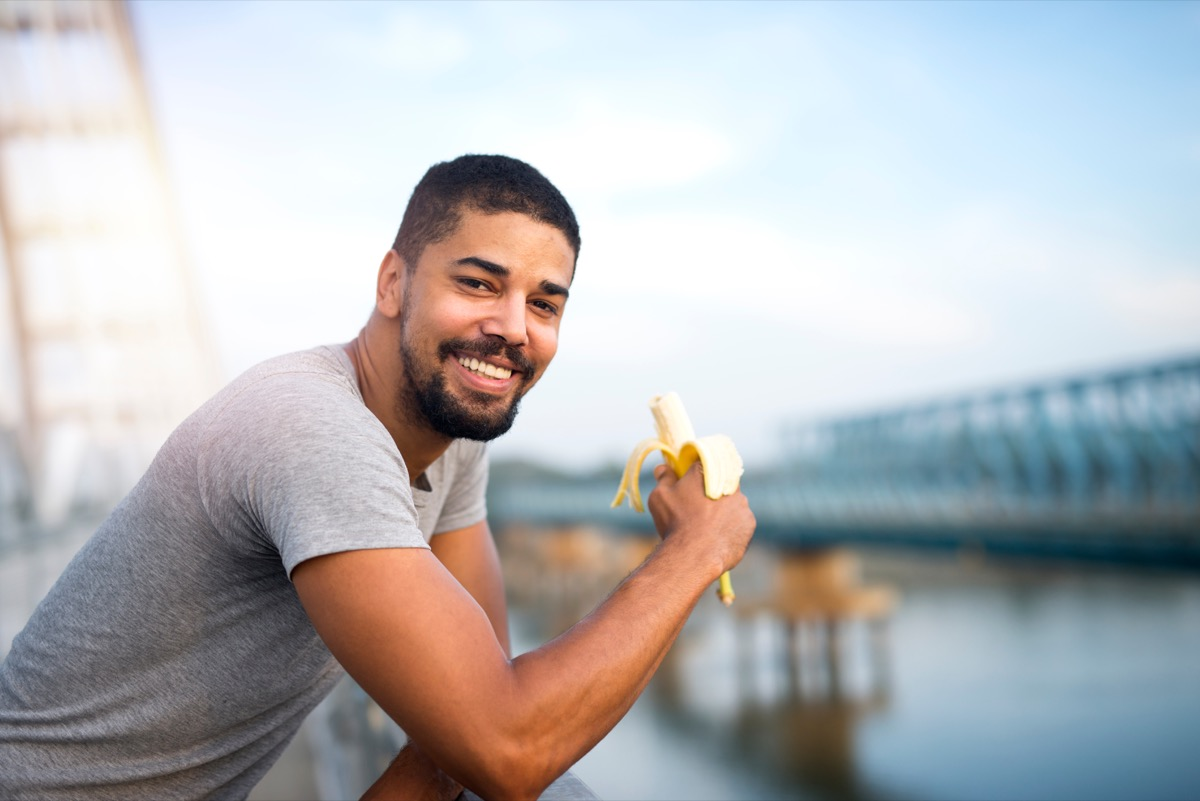 Black man eating a banana outside