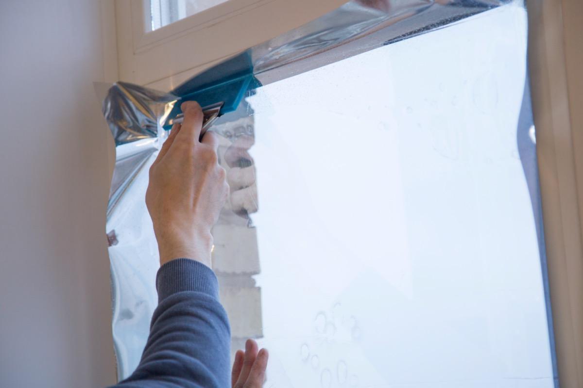 man installing reflective window film