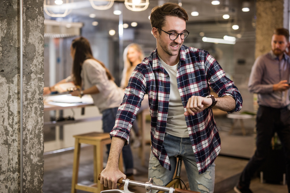 White man leaving work early after checking his watch in casual workplace