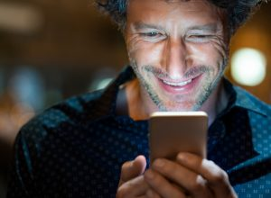 Closeup face of happy mature businessman messaging on cellphone at night on the street with the lights of the road blurred in the background.